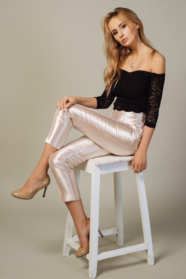 La muchacha rubia hermosa con los pantalones elegantes se sienta en una silla imagen de archivo