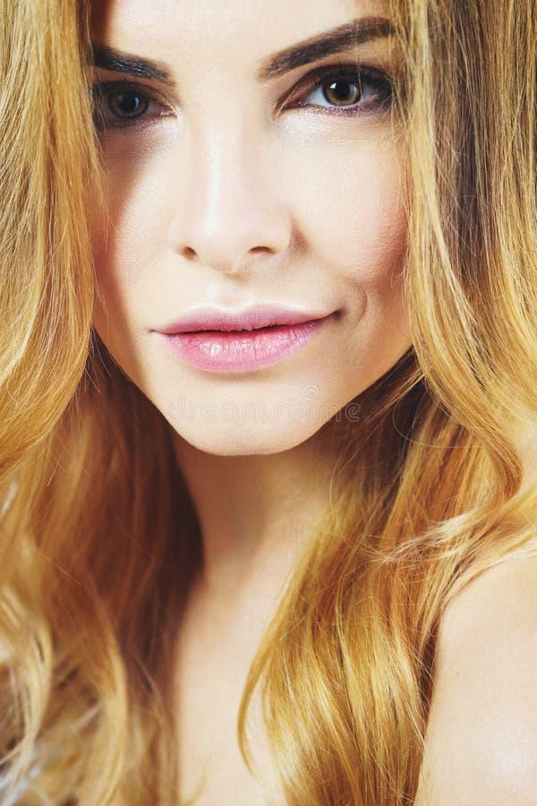 La muchacha rubia hermosa con una sonrisa mira directamente la cámara imagen de archivo libre de regalías