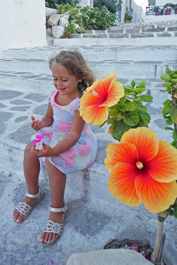 La muchacha rubia hermosa de 3-4 años juega feliz con las flores en Parikia, Paros, Grecia foto de archivo