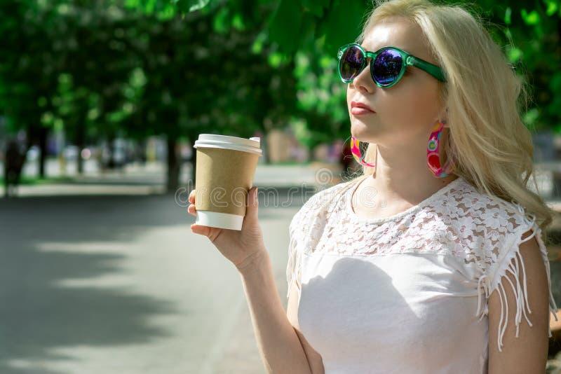 La muchacha rubia hermosa en la ciudad está bebiendo el café Sesión de foto de la calle Taza gris con una tapa blanca y un lugar  imágenes de archivo libres de regalías