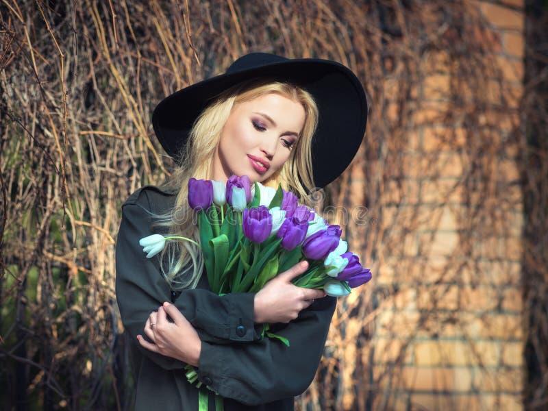 La muchacha rubia hermosa en un sombrero negro está gozando del ramo de los tulipanes foto de archivo libre de regalías