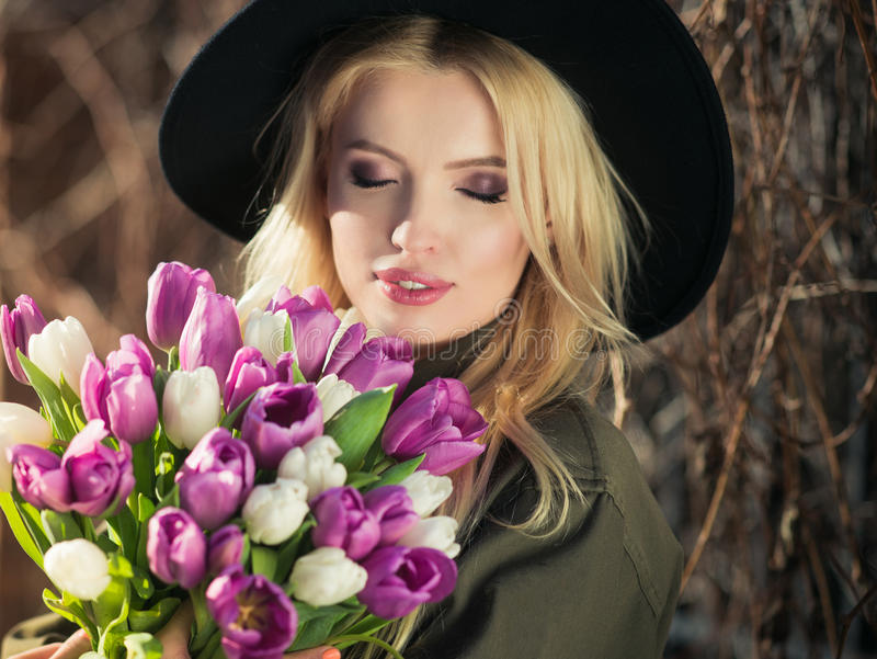 La muchacha rubia hermosa en un sombrero negro está gozando del ramo de los tulipanes imágenes de archivo libres de regalías