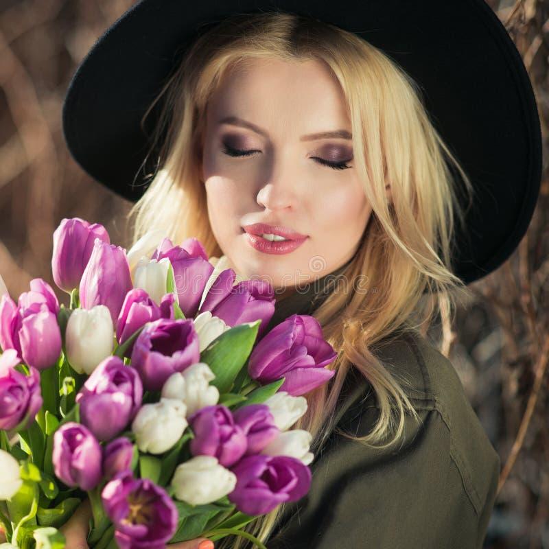 La muchacha rubia hermosa en un sombrero negro está gozando del ramo de los tulipanes imagen de archivo libre de regalías