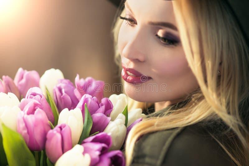 La muchacha rubia hermosa en un sombrero negro está gozando del ramo de los tulipanes imagenes de archivo