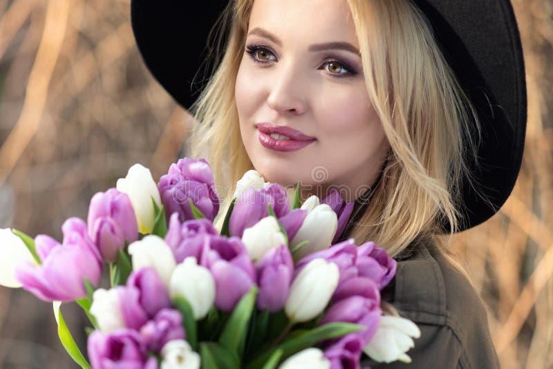 La muchacha rubia hermosa en un sombrero negro está gozando del ramo de los tulipanes fotografía de archivo libre de regalías