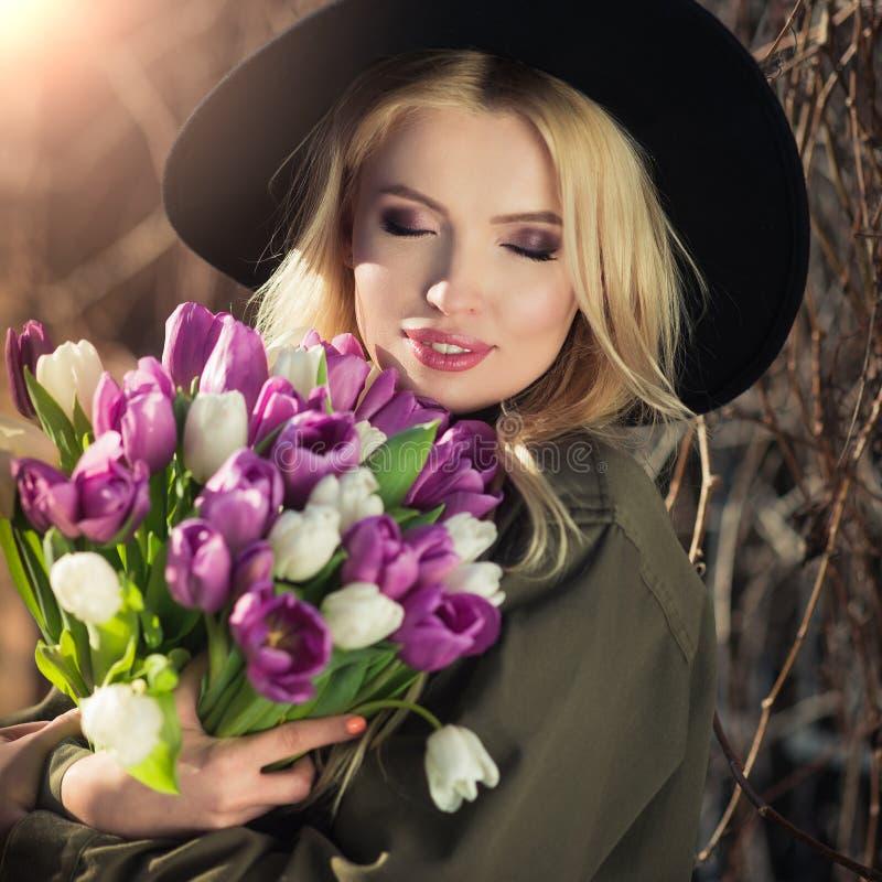 La muchacha rubia hermosa en un sombrero negro está gozando del ramo de los tulipanes fotografía de archivo