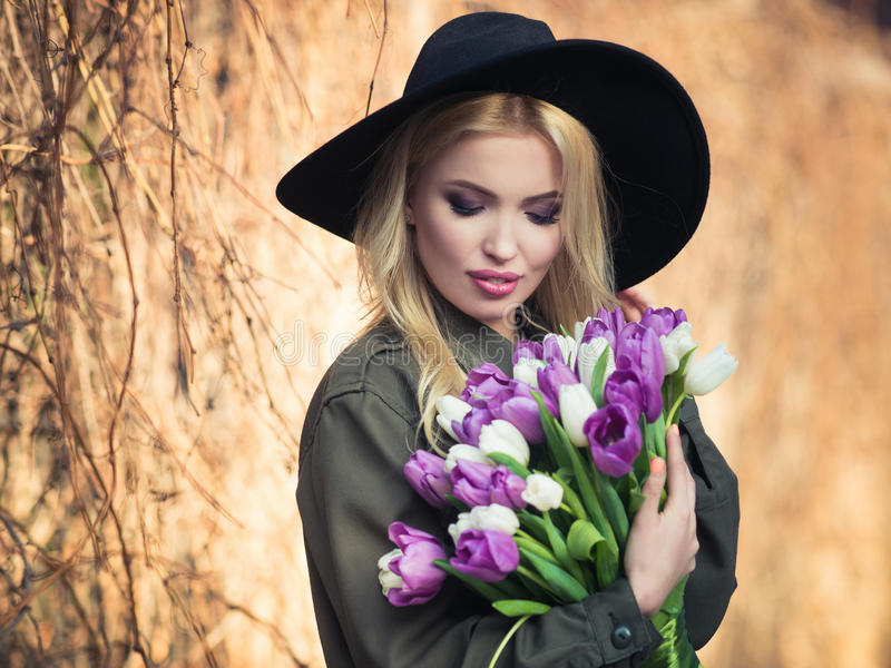 La muchacha rubia hermosa en un sombrero negro está gozando del ramo de los tulipanes foto de archivo