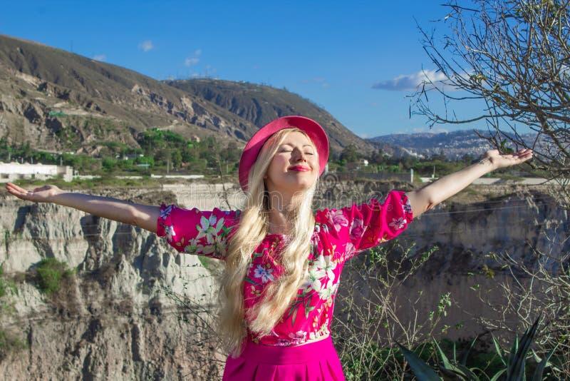 La muchacha rubia hermosa en un sombrero se coloca con los brazos extendidos En el fondo una montaña y un barranco Feliz fotografía de archivo