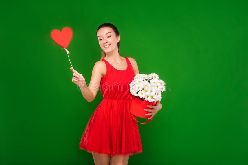 La muchacha rubia hermosa en un vestido rojo sostiene un corazón en sus manos y un ramo de manzanillas imagenes de archivo