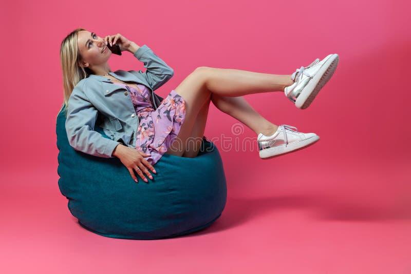 La muchacha rubia hermosa en una chaqueta azul y los sundress púrpuras se sienta en una silla verde del bolso con sus piernas de  imagen de archivo