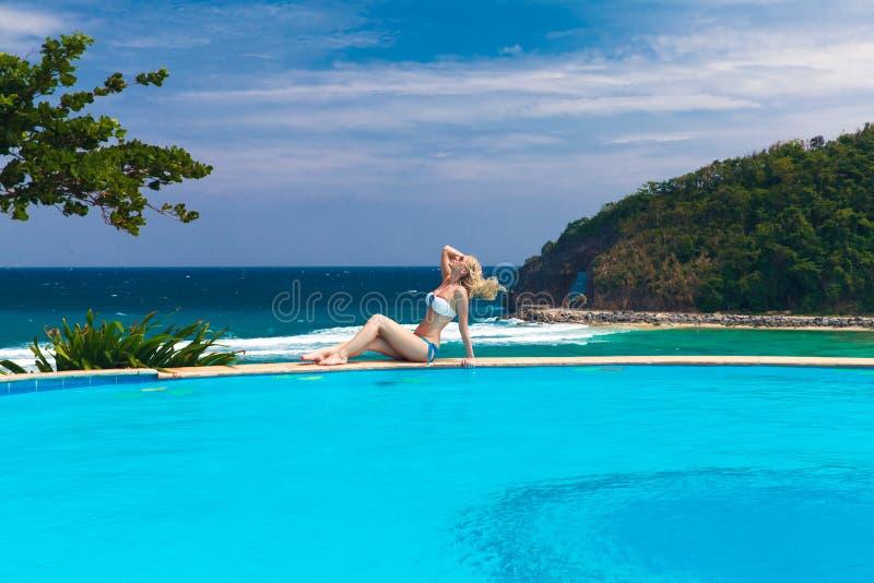 La muchacha rubia hermosa joven está al lado de la piscina Mar tropical adentro imagenes de archivo