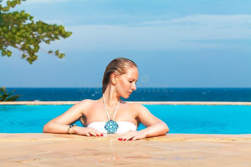 La muchacha rubia hermosa joven está en la piscina Mar tropical en imagenes de archivo