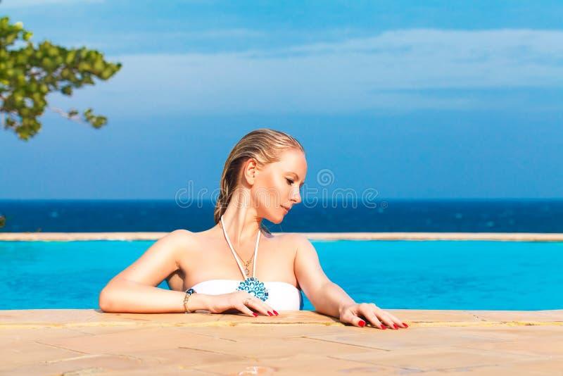 La muchacha rubia hermosa joven está en la piscina Mar tropical en foto de archivo