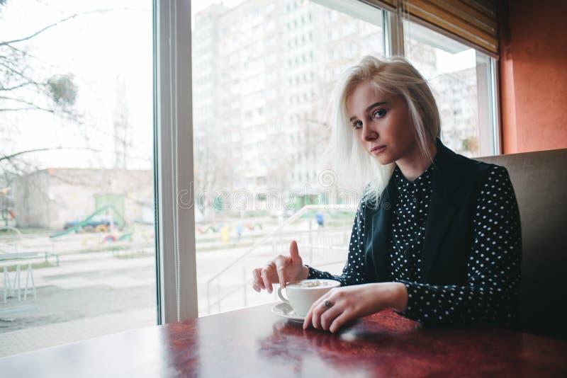 La muchacha rubia hermosa joven se vistió en la sentada negra en el café con una taza de café caliente imagen de archivo
