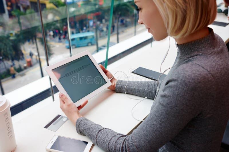 La muchacha rubia hermosa joven utiliza el ordenador portátil y el teléfono mientras que trabaja viaje usando la conexión inalámb imagenes de archivo