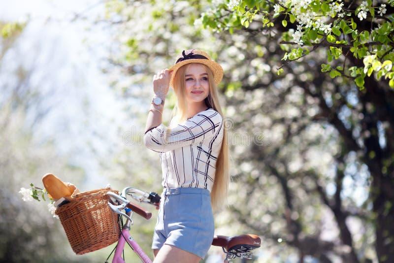 La muchacha rubia hermosa sostiene una bicicleta con una cesta de flores, y sonríe una sonrisa dulce visten a la muchacha en un b imagenes de archivo
