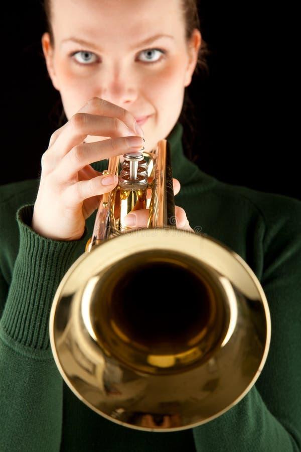 La muchacha rubia hermosa sostiene una trompeta de oro foto de archivo libre de regalías