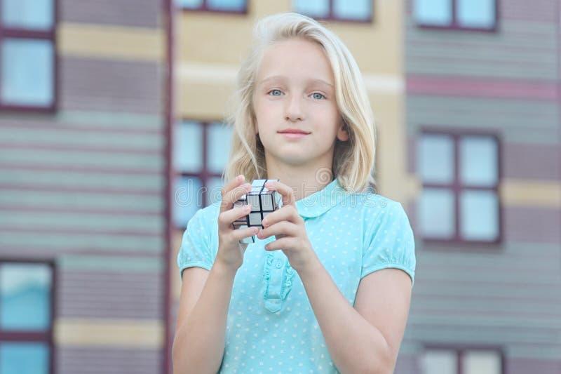 La muchacha rubia hermosa y lista del niño soluciona un rompecabezas del cubo del espejo imagenes de archivo