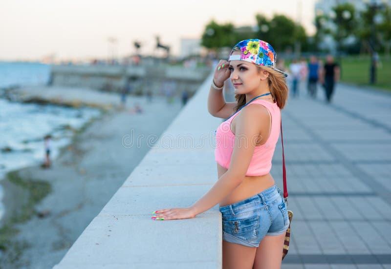 La muchacha rubia joven atractiva en pantalones cortos del dril de algodón se coloca en la costa de la ciudad y mira el mar imagenes de archivo