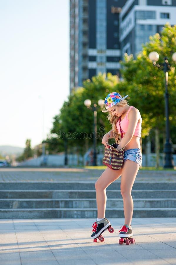 La muchacha rubia joven atractiva que patina en los rodillos del vintage traga la calle fotos de archivo