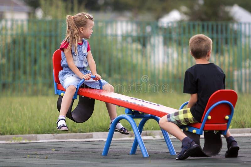 La muchacha rubia joven del preescolar de dos niños con la cola de caballo larga y el escolar lindo balancean en la oscilación en imagenes de archivo