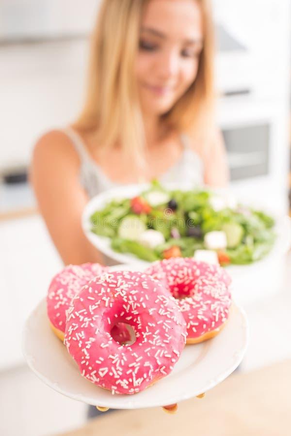 La muchacha rubia joven en el desayuno o la cena en la cocina casera elige entre el buñuelo y la ensalada vegetal imágenes de archivo libres de regalías