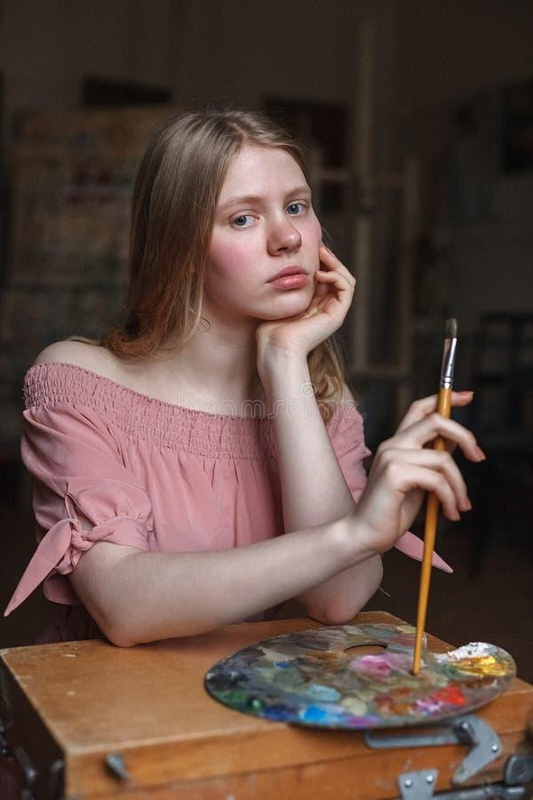 La muchacha rubia joven en vestido rosado descansa cuidadosamente su cabeza en su brazo y sostiene el cepillo al lado de la palet foto de archivo libre de regalías