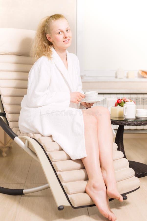 La muchacha rubia joven está bebiendo té en salón del balneario mujer en la capa blanca que sostiene una taza en sus manos foto de archivo libre de regalías