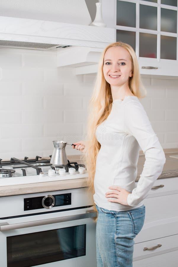 La muchacha rubia joven hace el café fotos de archivo libres de regalías