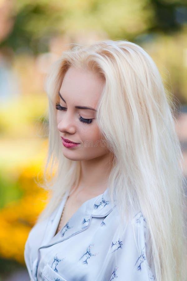 La muchacha rubia joven hermosa con una cara bonita y una sonrisa hermosa observa El retrato de una mujer con el pelo largo y sor imagen de archivo