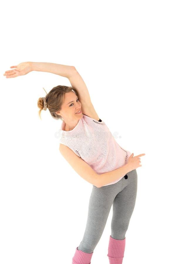 La muchacha rubia joven sonriente en polainas rosadas y un suéter, en las polainas grises que hacen yoga ejercita la gimnasia fotografía de archivo