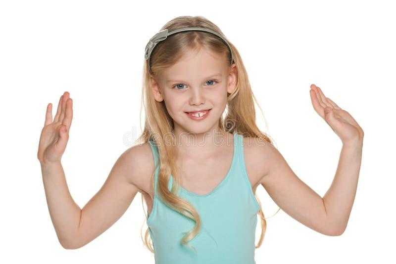 La muchacha rubia lanza para arriba sus manos foto de archivo