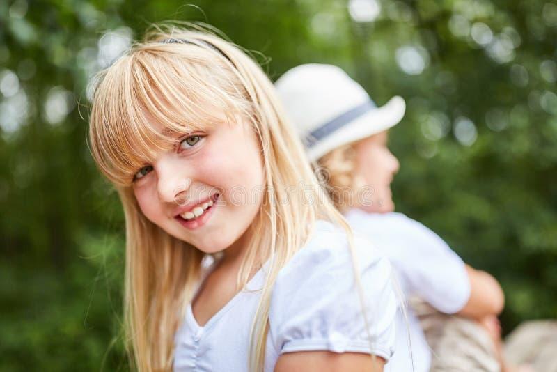 La muchacha rubia linda está sentando la sonrisa imagen de archivo
