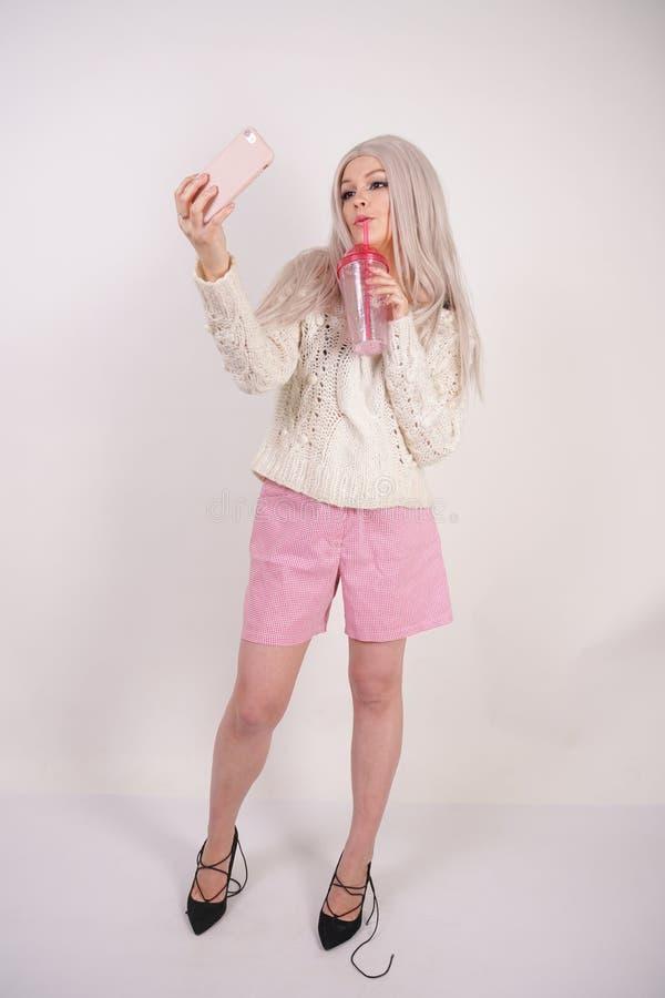 La muchacha rubia linda se coloca en ropa casual de moda, toma un selfie en su smartphone y sostiene una taza transparente rosada imagen de archivo libre de regalías