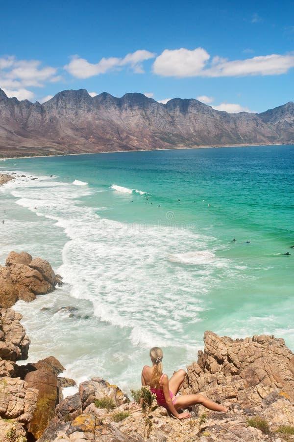 La muchacha rubia mira la playa majestuosa foto de archivo