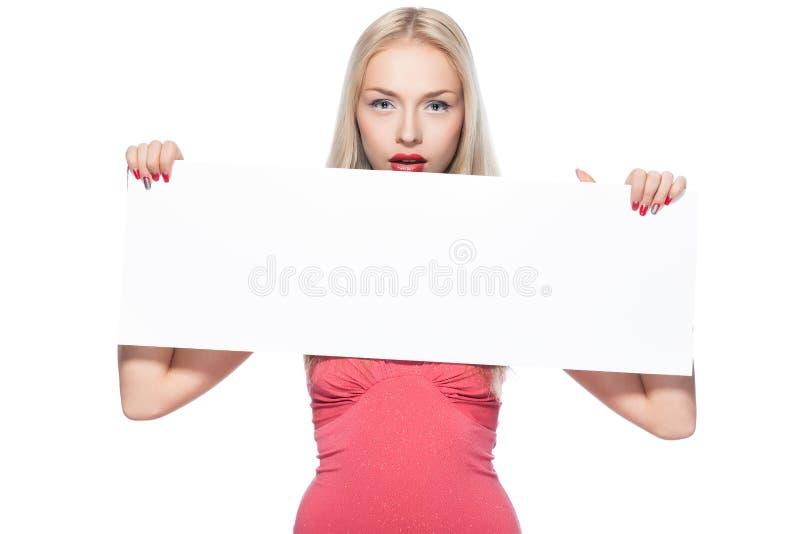La muchacha rubia muestra el cartel. imagenes de archivo