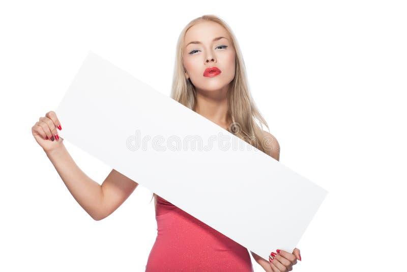 La muchacha rubia muestra el cartel. foto de archivo