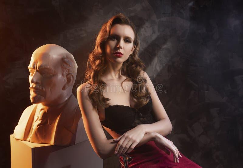 La muchacha rubia pechugona patilarga atractiva hermosa que lleva una falda roja y un cuerpo negro se sienta en una silla en la e imágenes de archivo libres de regalías