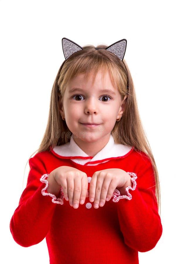 La muchacha rubia sonriente feliz en un vestido rojo con los oídos de un gato congriega en el fondo aislado blanco, llevando a ca imagen de archivo libre de regalías