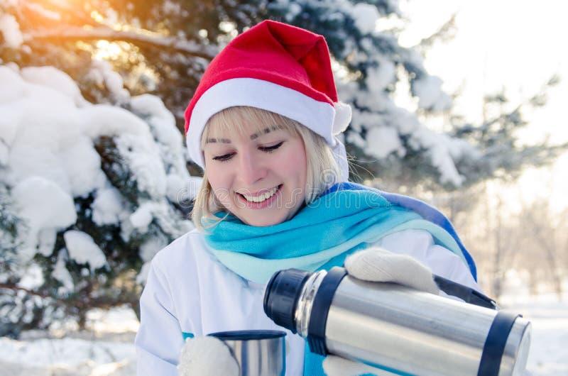 La muchacha rubia sonriente hermosa en un sombrero rojo de la Navidad vierte té caliente en una taza imagen de archivo