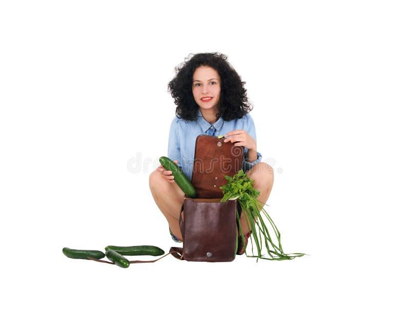 La muchacha saca del pepino del bolso fotos de archivo libres de regalías