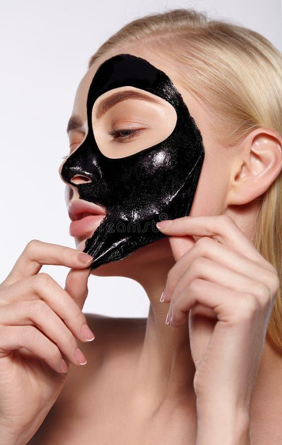 La muchacha saca la máscara cosmética negra de su cara imagenes de archivo