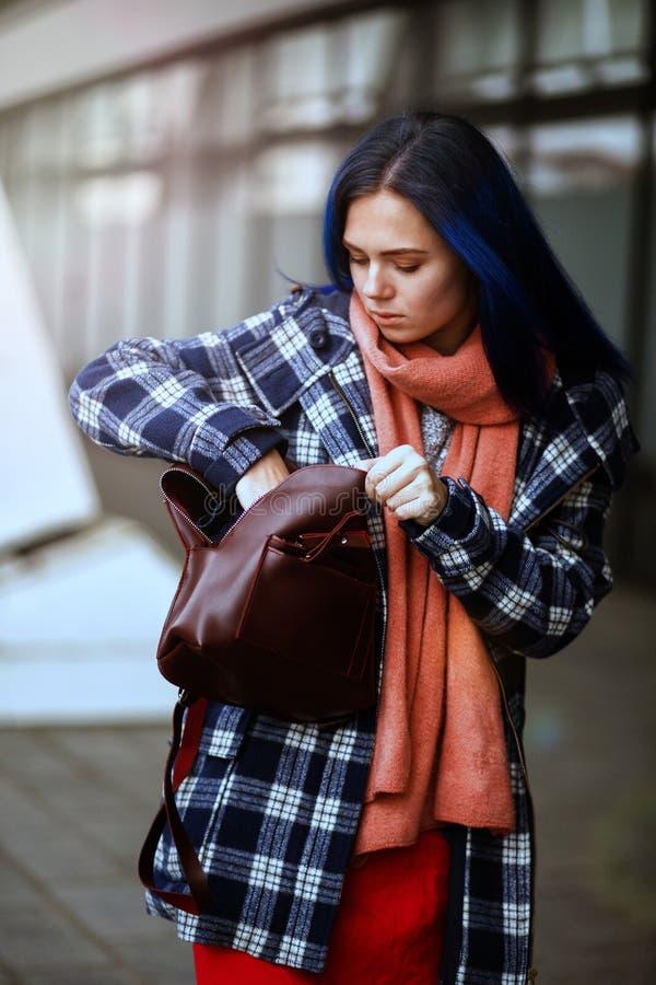 La muchacha saca un cuaderno del bolso fotografía de archivo libre de regalías