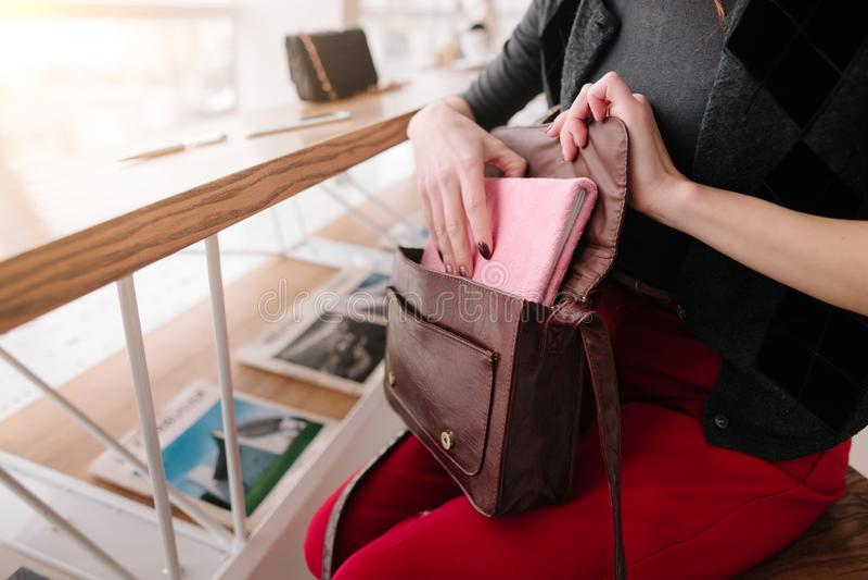 La muchacha saca una libreta de su bolso fotografía de archivo