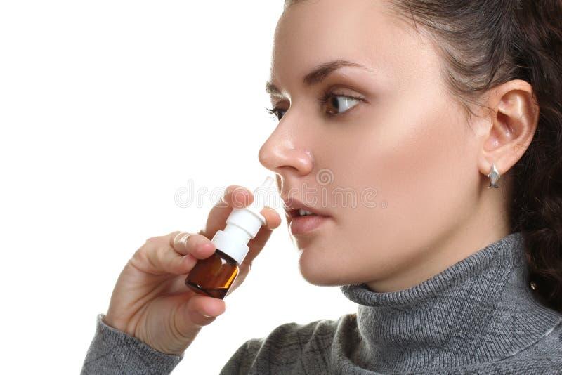 La muchacha salpica el espray en la nariz foto de archivo libre de regalías