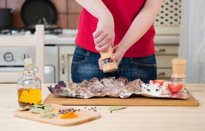 La muchacha sazona la carne con pimienta en las especias y las verduras de una tabla Manos de la mujer imagen de archivo libre de regalías
