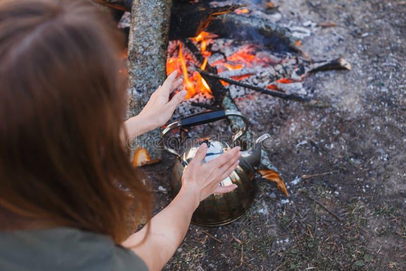 La muchacha se calienta las manos sobre la caldera por el fuego fotografía de archivo libre de regalías