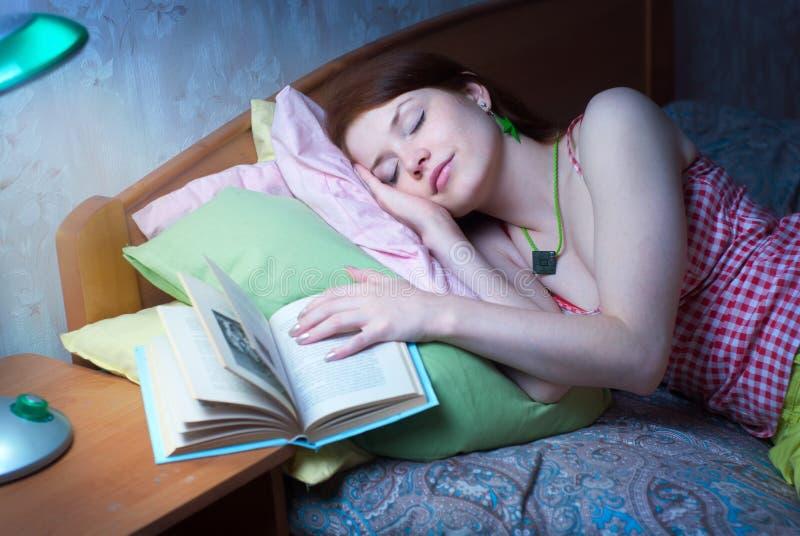 La muchacha se cayó dormido con un libro fotos de archivo libres de regalías