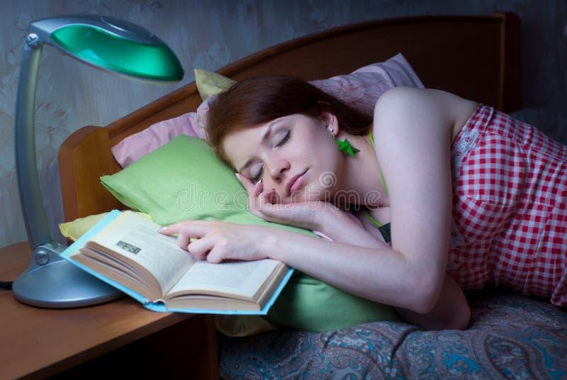 La muchacha se cayó dormido con un libro foto de archivo