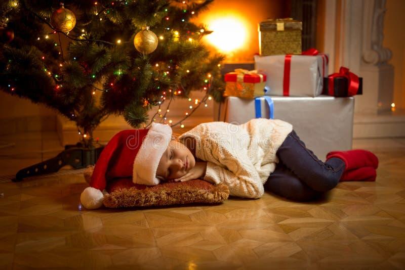 La muchacha se cayó dormido debajo del árbol de navidad mientras que esperaba Papá Noel imagen de archivo